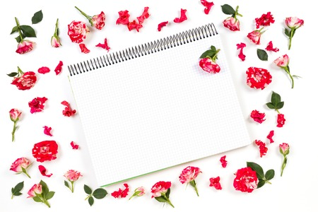 Open paper notebook and rose frame. Flat lay, top view