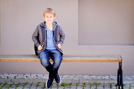 Boy with backpack sitting on the bench near the school