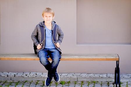 Jongen met rugzak zit op de bank in de buurt van de school
