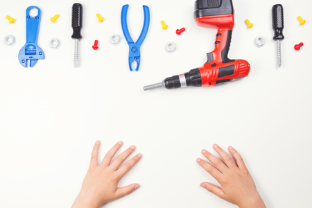 bolts and nuts: Top view on childs hands with colorful toys tools on the white background. Stock Photo