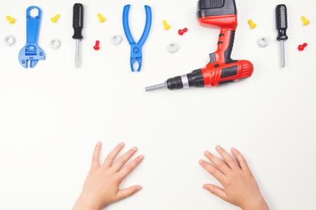 Vista superior en las manos de los niños con herramientas de juguetes coloridos sobre el fondo blanco.