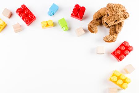 Kinderen speelgoed achtergrond met teddy beer en kleurrijke bakstenen Stockfoto