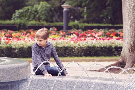 Child sitting near the fountain in the city park Stock Photo