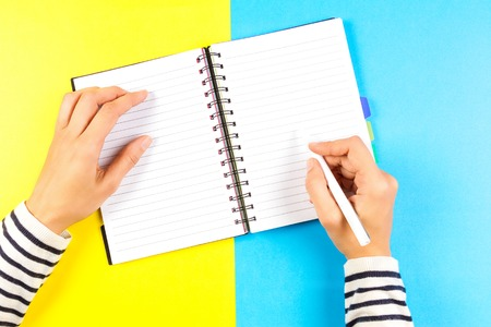 Woman hand writing in notebook over blue and yellow background. Top view