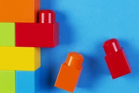 Colorful plastic construction blocks on blue background