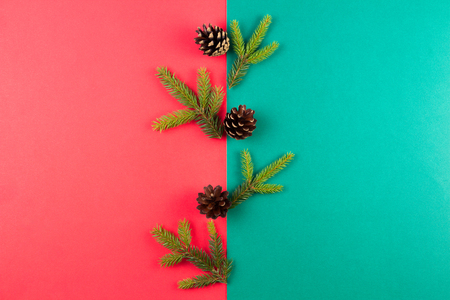 Christmas composition. Fir tree branches and pine cones arranged on red and green background. Top view, flat lay. Stock Photo