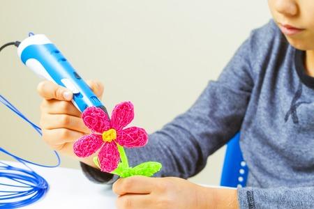 De handen die van jonge geitjes bloem met 3d drukpen maken