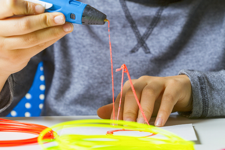 learning new skills: Kid hands with 3d printing pen, colorful filaments on white desk.