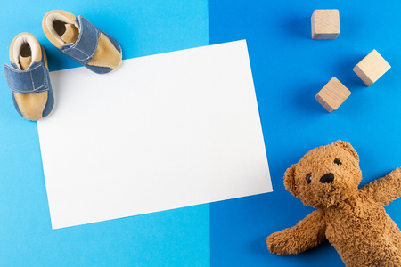 É um menino, tema azul chá de bebê ou berçário fundo com cartão em branco, teddy besr, blocos de madeira e sapatos de bebê