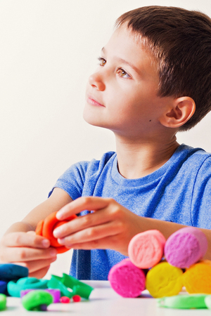 sculp: Boy playing and creating from modeling clay or plasticine