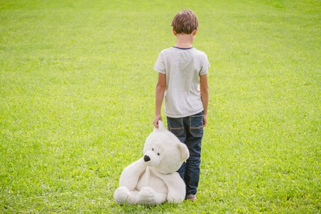 Sad child with teddy bear standing in the meadow. Child looking down. Back view. Stock Photo