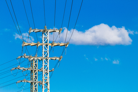 High voltage power lines and electric transmission pylon with blue sky background Stock Photo