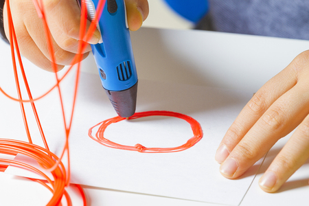 Kid hands with 3d printing pen, colorful filaments on white desk.