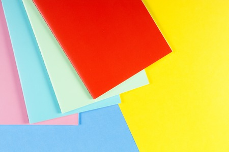 Colorful notebooks on blue and yellow background Archivio Fotografico