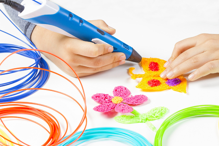 Kid hand holding blue 3d printing pen and making new item