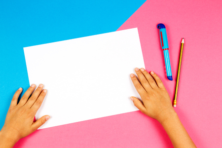 Kids hands with white blank paper, pen and pencil on blue and pink background 免版税图像