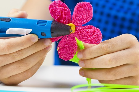 Kid hands holding blue 3d printing pen and making new item