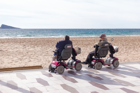 Benidorm, Spain - January 14, 2018: Seniors on mobility scooters looking to the sea in Benidorm, Spain