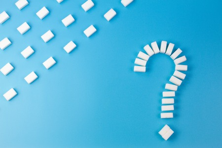 Sugar cubes shaped as a question mark sign on blue background.