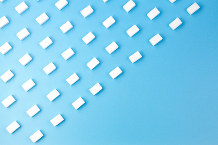 White sugar cubes arranged in diagonal lines on blue background