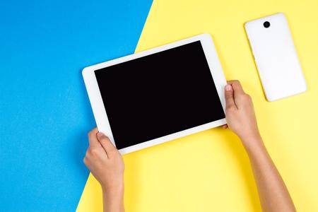 青と黄色の背景にタブレットコンピュータを保持する子供の手