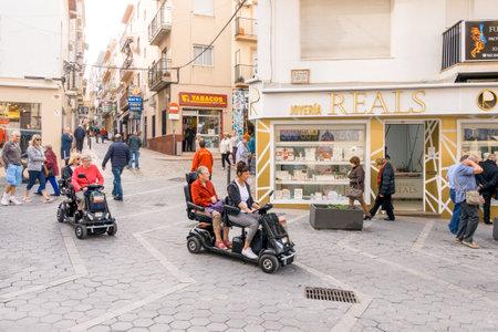 Benidorm, Spanien - 29. Januar 2018: Womans mit gemieteten Mobilitätsrollern in der Straße von Benidorm, Spanien