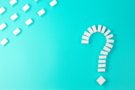 Sugar cubes shaped as a question mark sign on turquoise background.