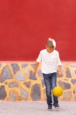 Boy playing with soccer ball outdoors Stock Photo