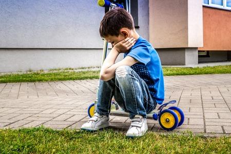 Upset sad kid sitting on the scooter outdoors Stock Photo