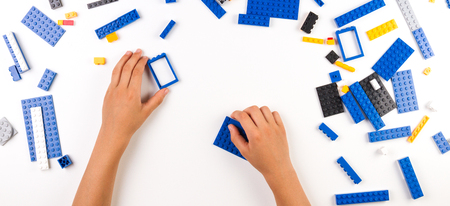 Close up of childs hands playing with colorful plastic bricks at the table Stock Photo