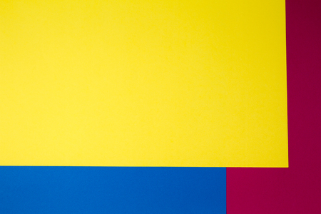 Color papers geometry flat composition background with yellow, red and blue tones
