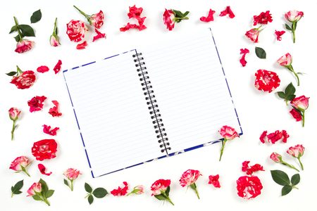 Flowers composition. Frame made of rose flowers. Open notebook or diary in the middle. Flat lay, top view Stock Photo