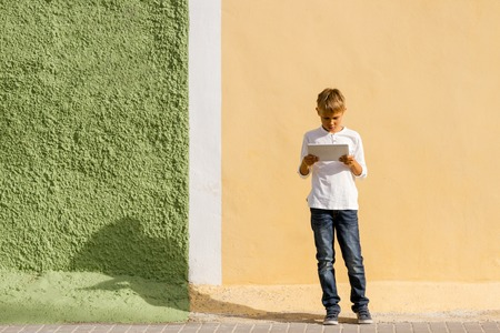 Child using tablet computer standing outdoors.