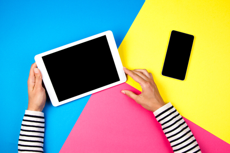 Womans hands with tablet computer and smartphone on colorful background. Stock Photo