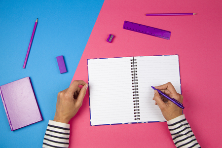 Woman hands writing to open notebook and office supplies on colorful background