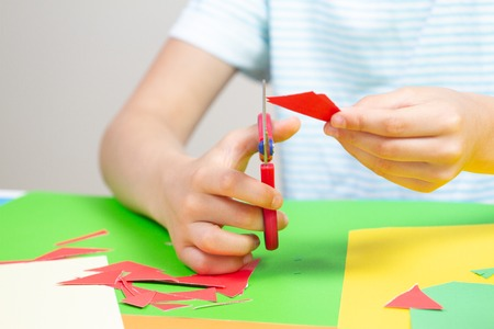Child hands cutting colored paper with scissors at the table