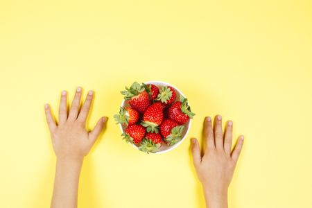 Kid hands and bowl with fresh strawberries on yellow background.