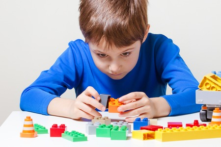 Child playing with colorful plastic construction toy blocks at the table.