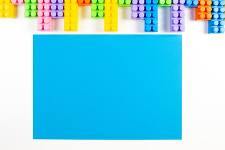 Colorful plastic construction blocks frame and blue blank card on white background 版權商用圖片