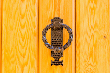 Vintage bronze door knocker on a yellow door