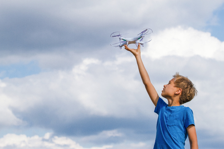 Child holding drone outdoors at summer day