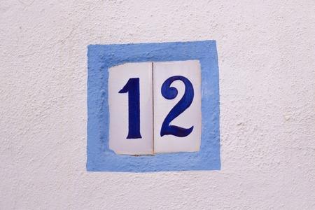 House number on ceramic tiles on white wall Standard-Bild