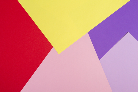 Color papers geometry flat composition background with violet, purple, pink, red, yellow tones.