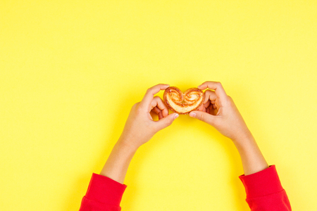 Kid hands holding cookie over yellow background Stock Photo
