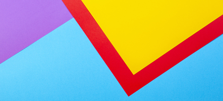 Color papers geometry flat composition background with yellow red violet and blue tones