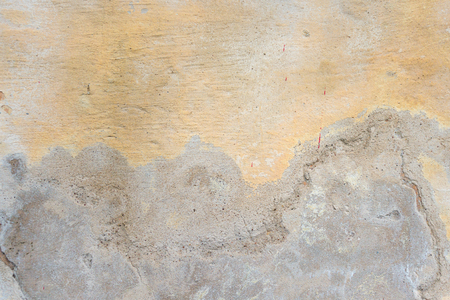 Textured grunge background. Old plastered wall with a multilayer cracked coating. Grunge texture with a deep pattern on yellow wall
