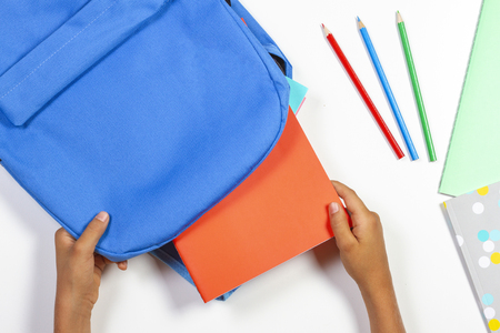Back to school, education concept. Kid hands packing backpack and preparing for school