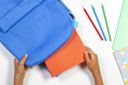 Retour à l'école, concept d'éducation. Kid mains emballage sac à dos et préparation pour l'école
