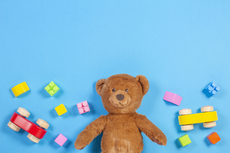 Baby kids toys background. Teddy bear, wooden car, colorful bricks on blue background
