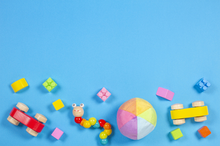 Baby kids toys background. Wooden car, colorful bricks and soft toys on blue background